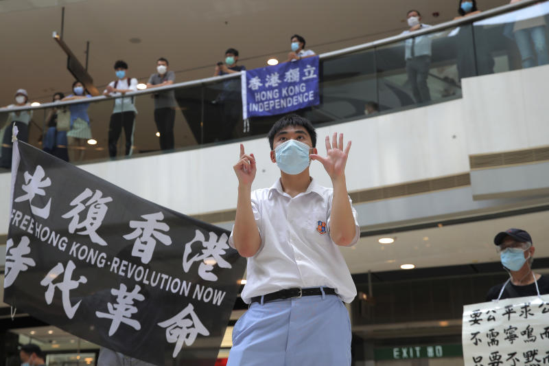 "A protester gestures with five fingers, signifying the ""Five demands - not one less"" in a shopping mall during a protest against China's national security legislation for the city, in Hong Kong, Friday, May 29, 2020. The British government says t it will grant hundreds of thousands of Hong Kong residents greater visa rights if China doesn't scrap a planned new security law for the semi-autonomous territory. U.K. Foreign Secretary Dominic Raab said about 300,000 people in Hong Kong who hold British National (Overseas) passports will be able to stay in Britain for 12 months rather than the current six. (AP Photo/Kin Cheung)"