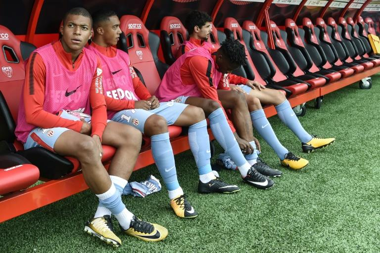 Monaco's forward Kylian Mbappe (L) sits on the bench during the French Ligue 1 football match against Dijon FCO August 13, 2017