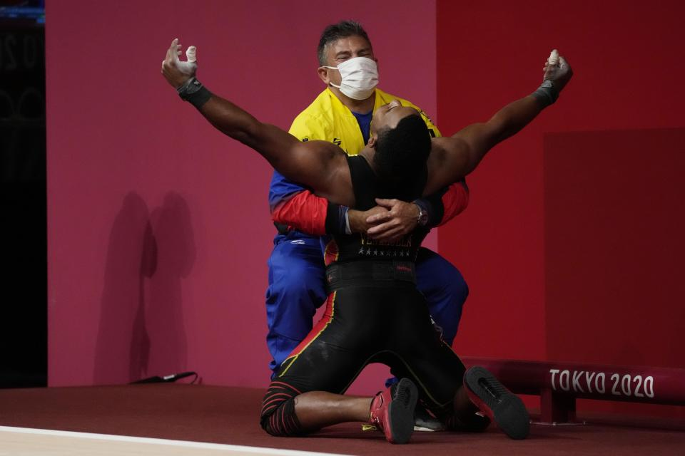 Julio Ruben Mayora Pernia of Venezuela celebrates after winning the silver medal in the men's 73kg weightlifting event, at the 2020 Summer Olympics, Wednesday, July 28, 2021, in Tokyo, Japan. (AP Photo/Luca Bruno)
