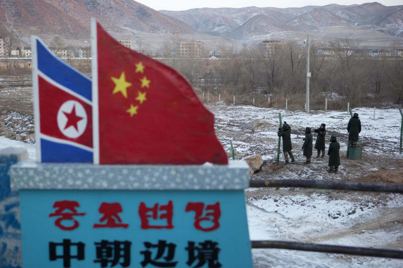 """In this Saturday, Dec. 8, 2012 photo, Chinese paramilitary policemen build a fence near a concrete marker depicting the North Korean and Chinese national flags with the words """"China North Korea Border"""" at a crossing in the Chinese border town of Tumen in eastern China's Jilin province. (AP Photo/Ng Han Guan)"""