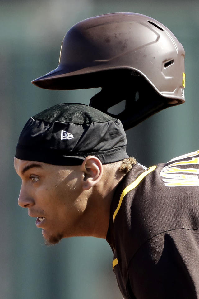 San Diego Padres' Josh Naylor looses his helmet as he advances safely to second base on a fly out by Manny Machado during the third inning of a spring training baseball game against the Kansas City Royals Monday, Feb. 24, 2020, in Surprise, Ariz. (AP Photo/Charlie Riedel)