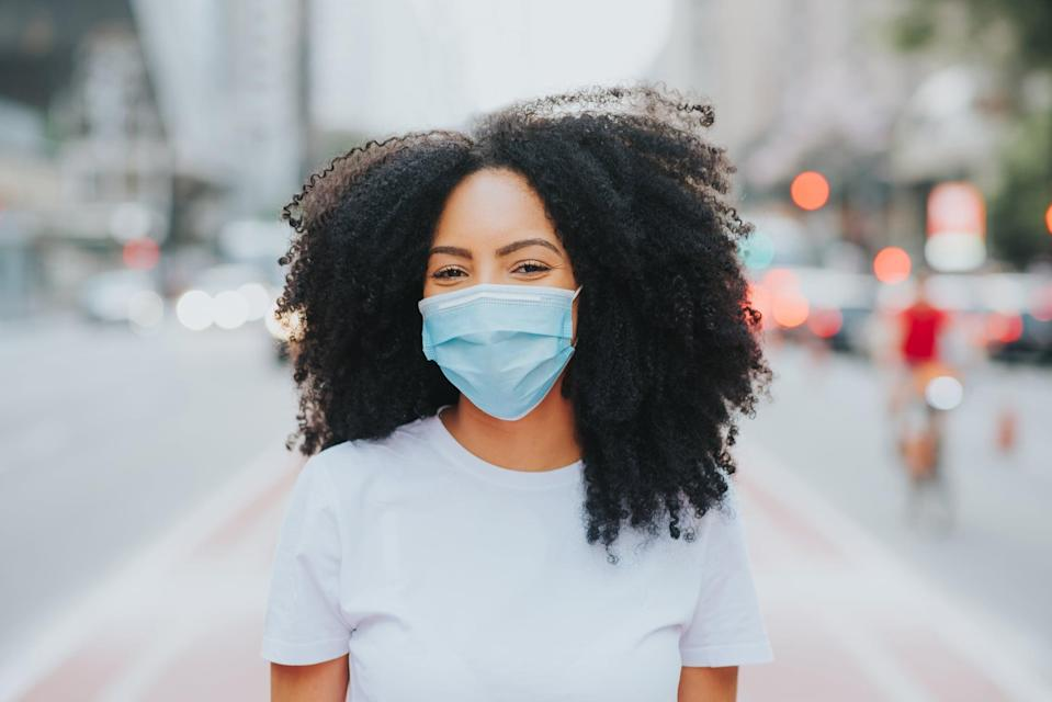Young woman in the city smiling behind the coronavirus face protection mask