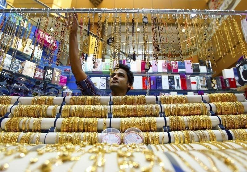 A salesman arranges jewellery at a shop at the gold souk in Deira