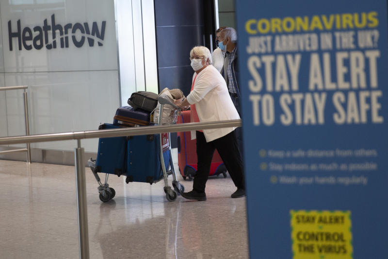 Passengers wearing face masks arrive on the first day of new rules that people arriving in Britain from overseas will have to quarantine themselves for 14 days to help stop the spread of coronavirus, at Heathrow Airpot in London, Monday, June 8, 2020. The British government has said that anyone caught not complying with the quarantine will face a fine. (AP Photo/Matt Dunham)