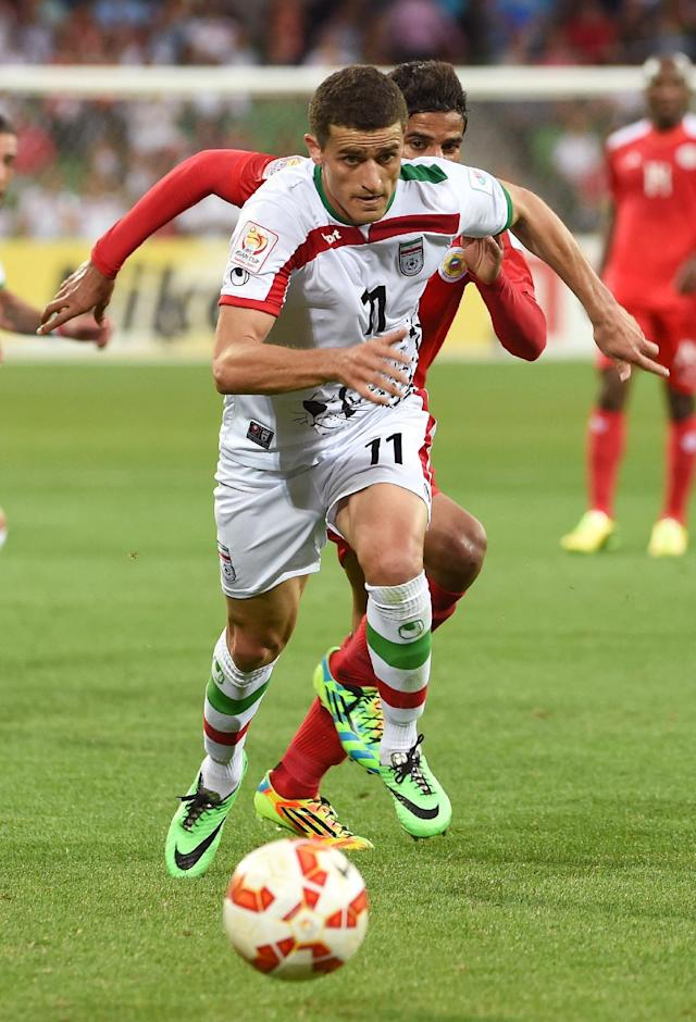 Iran's Vorya Ghafouri (front) runs through Bahrain defence during their AFC Asian Cup match, in Melbourne, on January 11, 2015 (AFP Photo/William West)