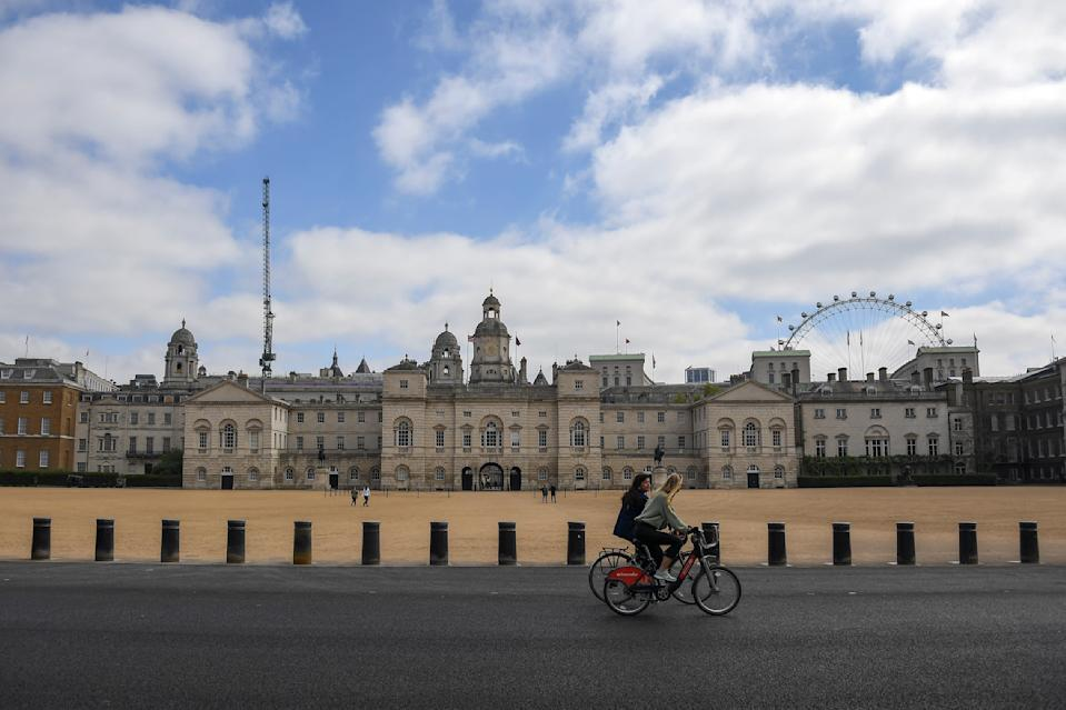 Two women ride bicycles past the Horse Guards Parade, during lockdown due to the coronavirus outbreak, in London, Saturday, April 25, 2020.(AP Photo/Alberto Pezzali)