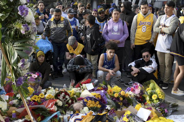 People gather at a memorial for Kobe Bryant near Staples Center Sunday, Jan. 26, 2020, in Los Angeles. Bryant, the 18-time NBA All-Star who won five championships and became one of the greatest basketball players of his generation during a 20-year career with the Los Angeles Lakers, died in a helicopter crash Sunday, Jan. 26, 2020. (AP Photo/Michael Owen Baker)