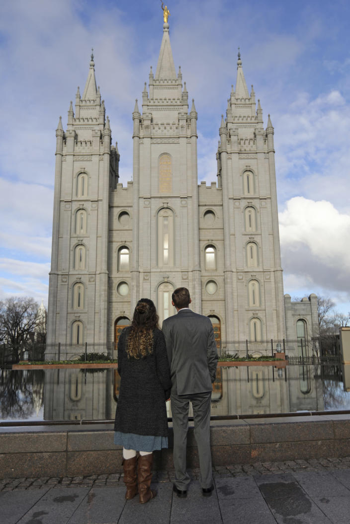 FILE - In this April 6, 2019, file photo, a couple looks at the Salt Lake City temple during the The Church of Jesus Christ of Latter-day Saints' two-day conference. The Church of Jesus Christ of Latter-day Saints added new language to the faith's handbook Friday, Dec. 18, 2020. imploring members to root out prejudice and racism, adding significance and permanence to recent comments by top leaders on one of the most sensitive topics in the church's history. (AP Photo/Rick Bowmer, File)