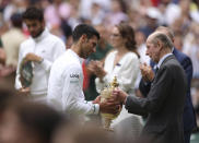 Prince Edward, the Duke of Kent, presents the winner's trophy to Serbia's Novak Djokovic after the men's singles final on day thirteen of the Wimbledon Tennis Championships in London, Sunday, July 11, 2021. (Steve Paston/Pool Via AP)