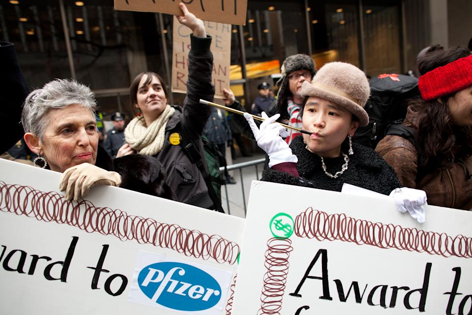 Occupy Wall Street protestor Laurie Wen, right, of Manhattan, mocks the super rich while holding protest signs during a march on the offices of pharmaceutical giant Pfizer, Wednesday, Feb. 29, 2012, in New York. There was a heavy police presence around the 42nd Street area as the demonstration began Wednesday morning. (AP Photo/John Minchillo)