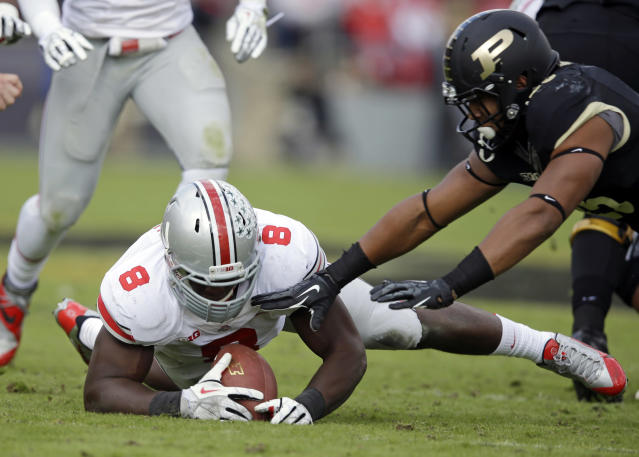 Ohio State defensive lineman Noah Spence, left, recovers a fumble by Purdue running back Brandon Cottom, right, during the first half of an NCAA college football game in West Lafayette, Ind., Saturday, Nov. 2, 2013. (AP Photo/Michael Conroy)