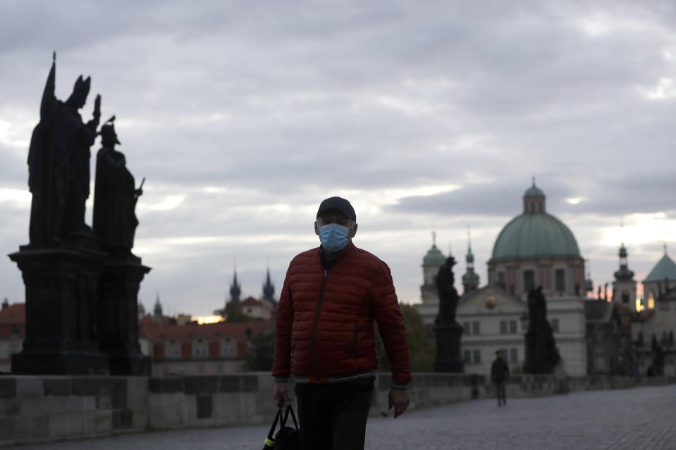 A man wearing a face mask crosses the medieval Charles Bridge in Prague, Czech Republic, Thursday, Oct. 8, 2020. Coronavirus infections in the Czech Republic have hit a new record high for the second straight day, surpassing 5,000 cases in one day for the first time. The new confirmed day-to-day increase reached 5,335 on Wednesday, according to Health Ministry figures. It is almost 900 more than the previous record on Tuesday. (AP Photo/Petr David Josek)
