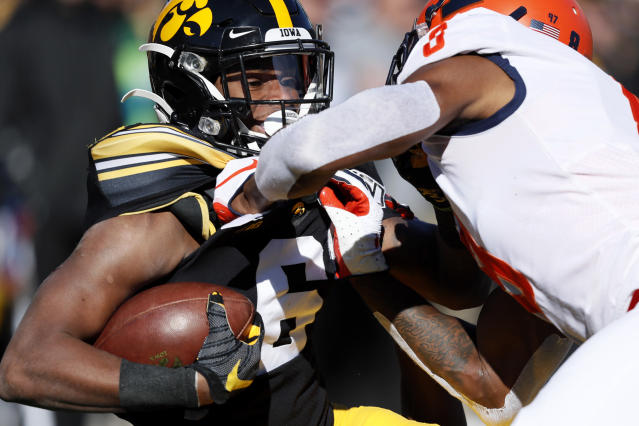 Iowa wide receiver Ihmir Smith-Marsette, left, is tackled by Illinois defensive back Nate Hobbs, right, after catching a pass during the first half of an NCAA college football game, Saturday, Nov. 23, 2019, in Iowa City, Iowa. (AP Photo/Charlie Neibergall)