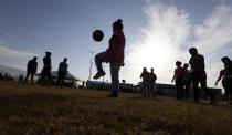 FILE - In this July 9, 2019, file photo, immigrants play soccer at the U.S. government's newest holding center for migrant children in Carrizo Springs, Texas. A federal volunteer at the Biden administration's largest shelter for unaccompanied immigrant children says paramedics were called regularly during her the two weeks she worked there. She said panic attacks would occur often after some of the children were taken away to be reunited with their families, dashing the hopes of those left behind. (AP Photo/Eric Gay, File)