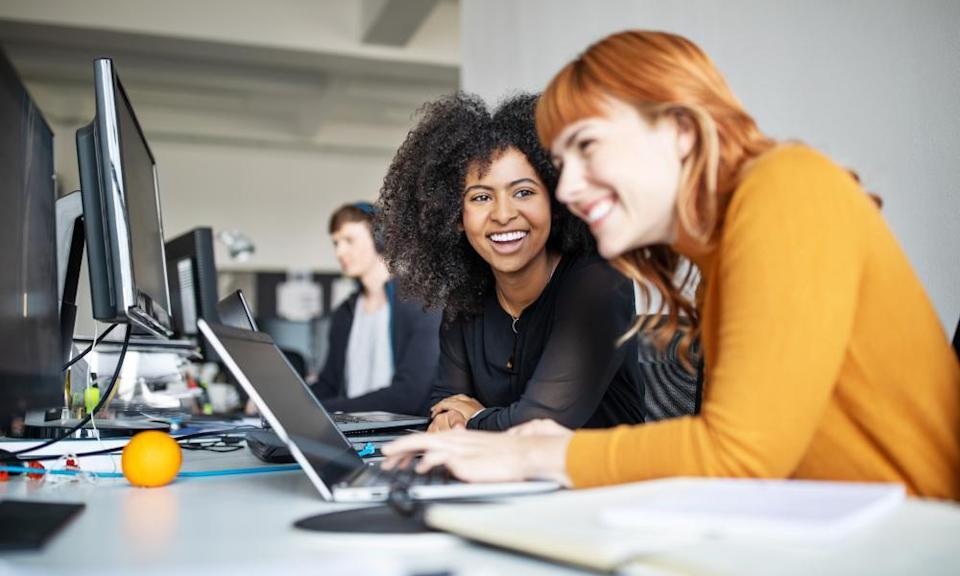 Two young women working together on laptop with male colleague in background.