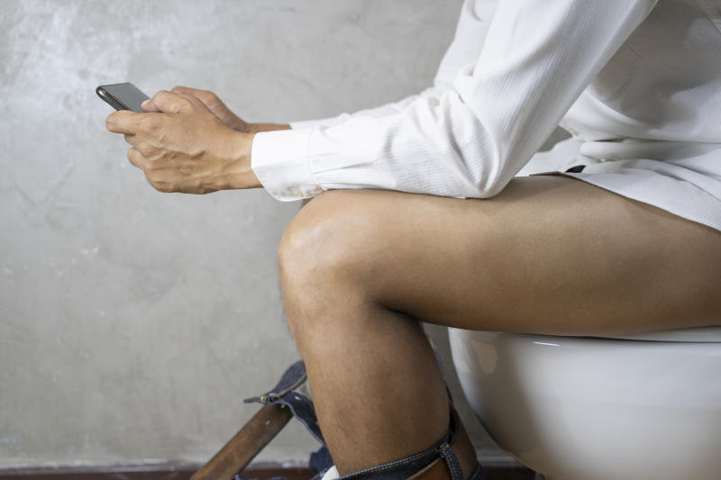 Man sitting on toilet and using smartphone - constipation concept.