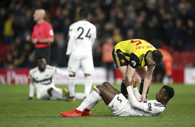 Fulham's Ryan Sessegnon is consoled by Watford's Craig Cathcart after the final whistle of the English Premier League soccer match against Watford at Vicarage Road, Watford, England, Tuesday, April 2, 2019. Three managers, 24 losses and around $130 million later, Fulham has been relegated from the Premier League. The London club's return to the English top flight will last just one season after its demotion was confirmed with a 4-1 loss at Watford on Tuesday. (Nigel French/PA via AP)