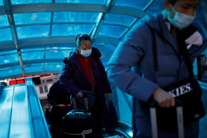 People wearing face masks carry their luggage as they use an escalator near Beijing Railway Station as the country is hit by an outbreak of the new coronavirus, in Beijing