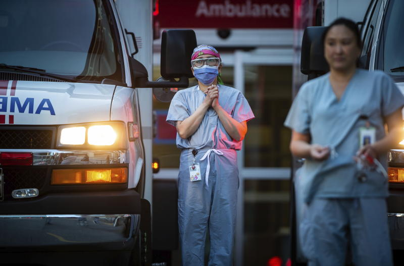 Healthcare workers at St. Paul's Hospital acknowledge applause and cheers from people outside the hospital, as a convoy of first responders with lights and sirens activated parade past to show support for the hospital staff, in Vancouver, British Columbia, Sunday, April 5, 2020. (Darryl Dyck/The Canadian Press via AP)