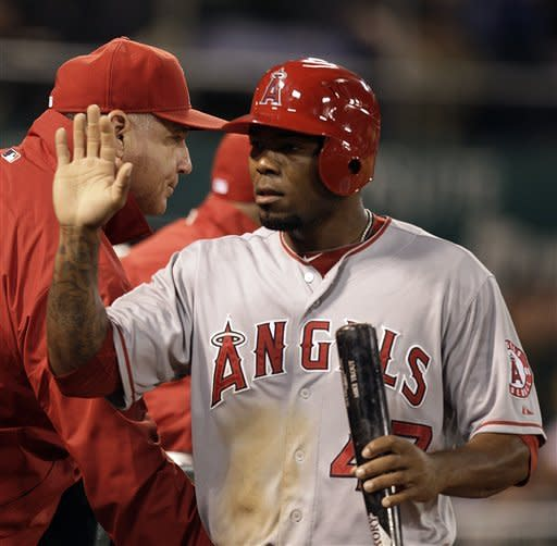 Los Angeles Angels' Howie Kendrick, right, celebrates as he passes manager Mike Scioscia after scoring against the Oakland Athletics during the fifth inning of a baseball game, Monday, May 21, 2012, in Oakland, Calif. Kendrick scored on a double by Mike Trout. (AP Photo/Ben Margot)