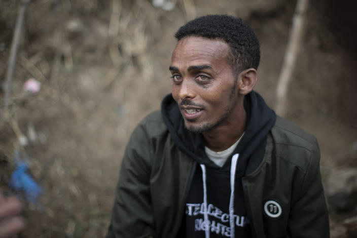 Clothes trader Gashaw Asmare, 22, who says he is striving for the kind of national unity that Ethiopia needs, speaks to The Associated Press in Gondar, in the Amhara region of Ethiopia Sunday, May 2, 2021. Ethiopia faces a growing crisis of ethnic nationalism that some fear could tear Africa's second most populous country apart, six months after the government launched a military operation in the Tigray region to capture its fugitive leaders. (AP Photo/Ben Curtis)