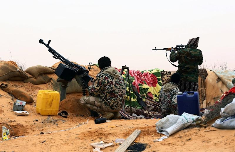 Fighters from the Fajr Libya (Libya Dawn) militia hold a position during clashes with forces loyal to Libya's internationally recognised government near the Wetia military air base on December 29, 2014 (AFP Photo/MahmudTurkia)