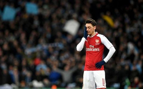 Ozil puts hand to his head - Credit: PA