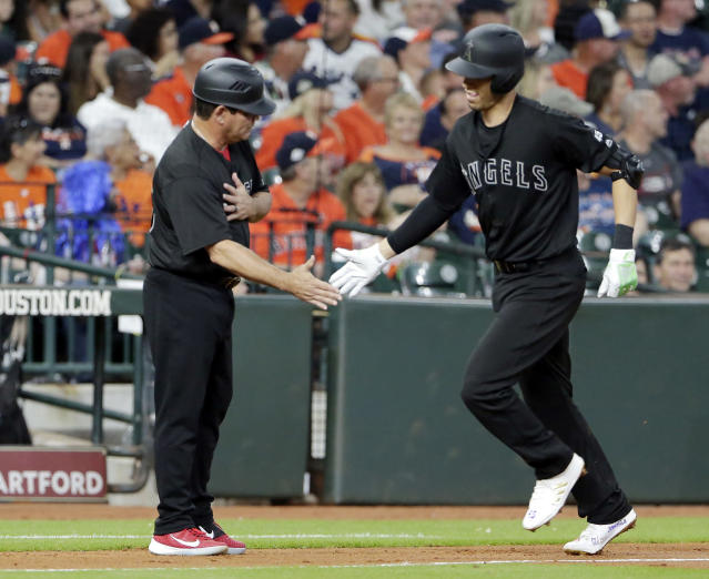 Los Angeles Angels shortstop Andrelton Simmons, right, low fives third base coach Mike Gallego, left, as he rounds the bases on his home run during the second inning of a baseball game against the Houston Astros Sunday, Aug. 25, 2019, in Houston. (AP Photo/Michael Wyke)