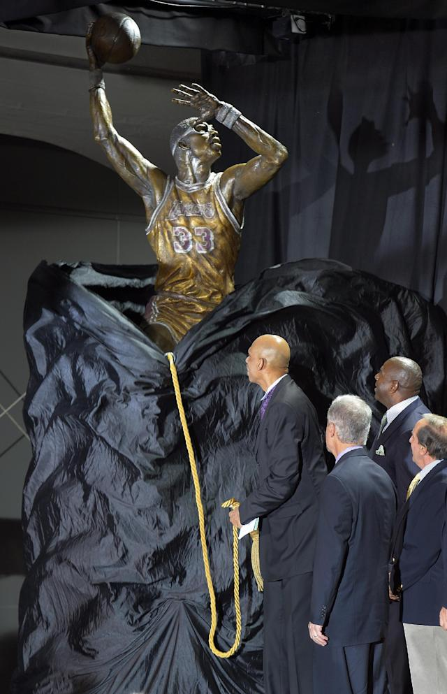 """Former Los Angeles Lakers center Kareem Abdul-Jabbar, left, unveils a statue of himself in front of Staples Center as Earvin """"Magic"""" Johnson, second from right, looks on, Friday, Nov. 16, 2012, in Los Angeles. (AP Photo/Mark J. Terrill)"""