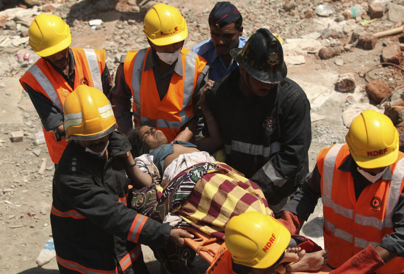 Indian rescue workers help an injured woman after a building collapse on the outskirts of Mumbai, India, Friday, April 5, 2013. The half-finished building that was being constructed illegally in a suburb of India's financial capital collapsed on Thursday, killing 35 people and injuring more than 50 others, police said Friday. (AP Photo)
