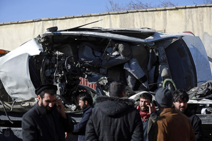Afghan security personnel inspect the site of a roadside bomb attack in Kabul, Afghanistan, Tuesday, Dec. 22, 2020. A roadside bomb tore through a vehicle in the Afghan capital of Kabul Tuesday, killing multiple people, police said. (AP Photo/Rahmat Gul)