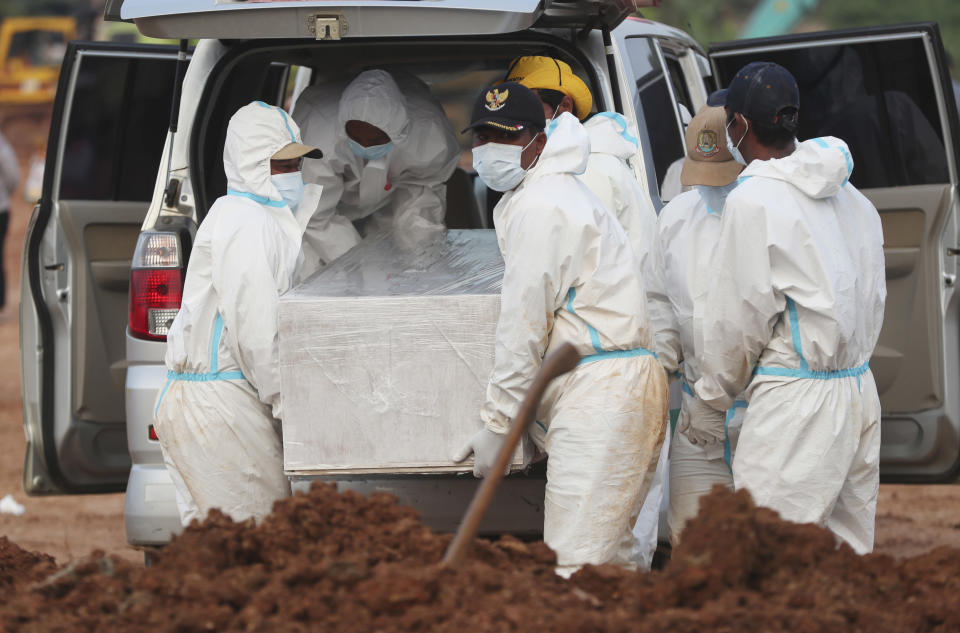Workers in protective gear carry a coffin of a COVID-19 victim for burial at the special section of the Pedurenan cemetery in Bekasi, West Java, Indonesia, Friday, July 30, 2021. Indonesia surpassed the grim milestone of 100,000 official COVID-19 deaths on Wednesday, Aug. 4, 2021, as the country struggles with its worst pandemic year fueled by the delta variant, with growing concerns that the actual figure could be much higher with people also dying at home. (AP Photo/Achmad Ibrahim)