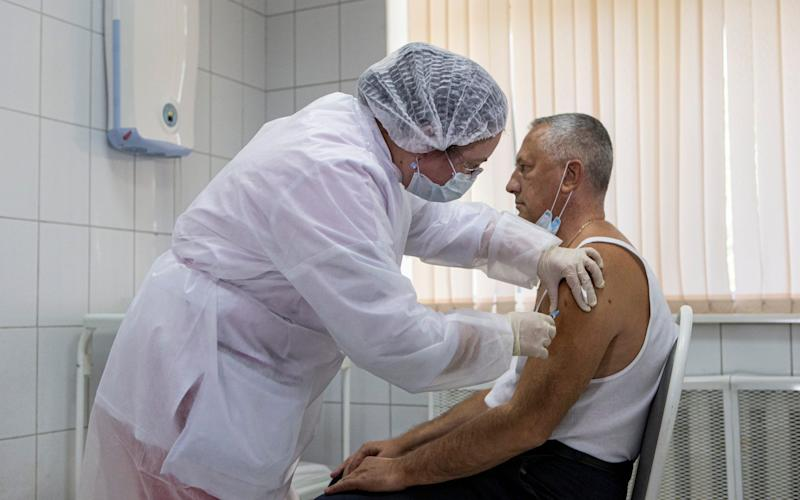 A Russian medical worker administers a shot of Russia's experimental Sputnik V coronavirus vaccine in Moscow, Russia, - AP
