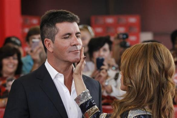"Simon Cowell, $90 million: Judge Paula Abdul jokingly touches the face of judge Simon Cowell as they arrive for the world premiere of the television series ""The X Factor"" at the Arclight Cinerama Dome in Hollywood, California September 14, 2011."