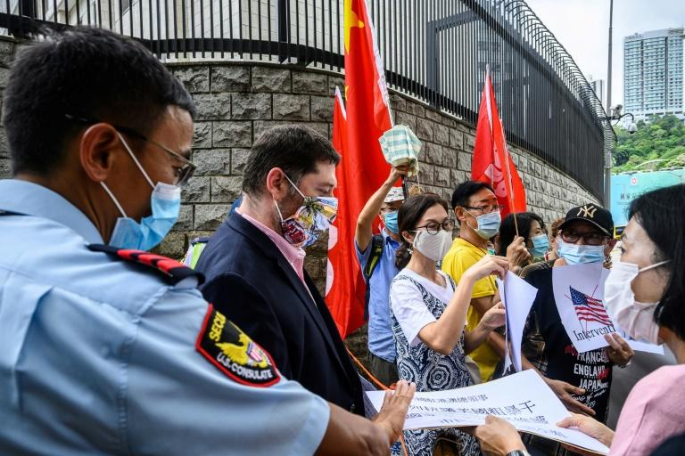 Pro-China activists holding placards and flags hand over a petition at the US consulate general in Hong Kong -- Washington has now imposed visa restrictions on Chinese officials over curbs on the city's autonomy (AFP Photo/Anthony WALLACE)