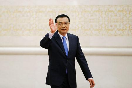 China's Premier Li Keqiang waves as he arrives for a news conference after the closing ceremony of China's National People's Congress (NPC) at the Great Hall of the People in Beijing