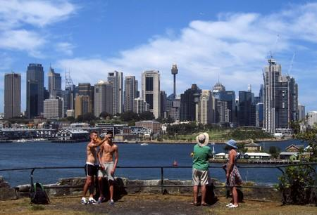 Tourists take photographs as they look from a nature reserve at the central business district of Sydney