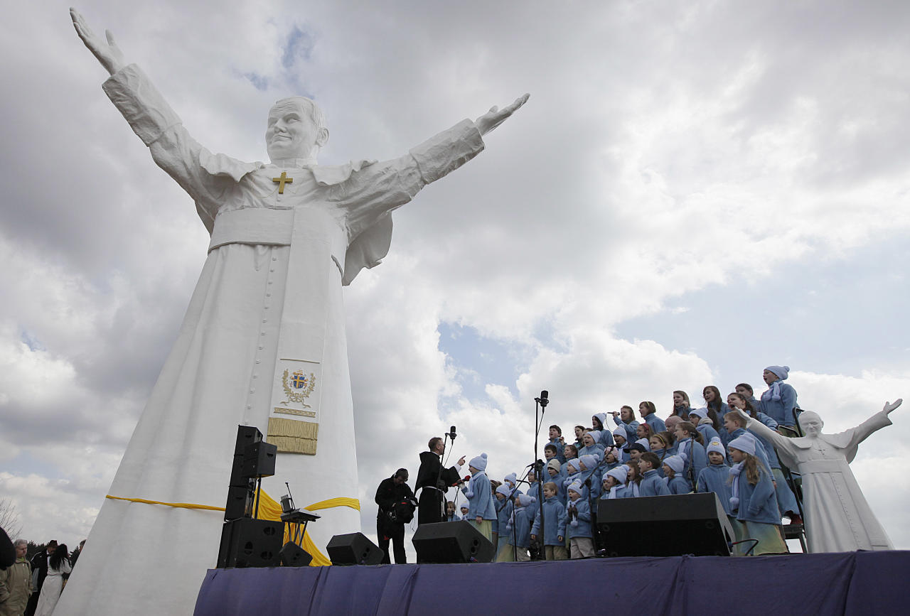 A children's choir takes part in the unveiling ceremony of the statue of the late Pope John Paul II in Czestochowa, Poland, on Saturday, April 13, 2013. Archbishop Waclaw Depo unveiled the 13.8-meter (45.3-foot) white fiberglass figure that was funded by a businessman, Leszek Lyson, in gratitude for what he believes was an intervention by the late pontiff in saving his drowning son. At right is a small replica statue. (AP Photo/Czarek Sokolowski)