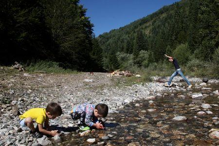 Children play in a river in the village of Haxhaj in Kosovo, near the border with Montenegro, August 28, 2016. REUTERS/Hazir Reka