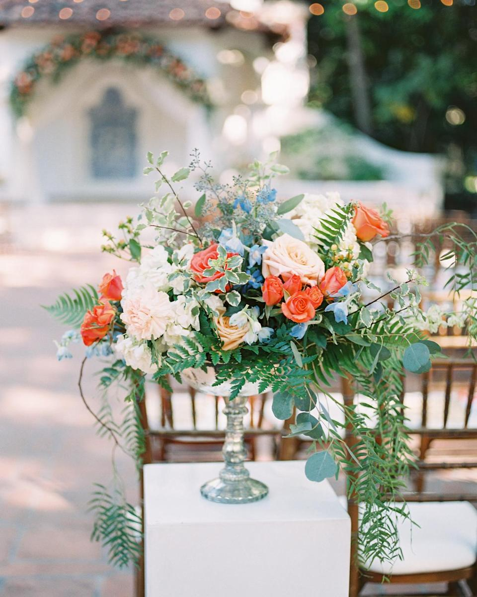 <p>Two floral urns marked the aisle's entrance; they were filled with dahlias, garden roses, spray roses, and other complementing flowers in ivory, white, peach, and coral, plus foliage for texture.</p>