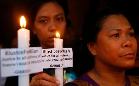 Protesters display placards and candles outside the wake for slain Delos Santos - Credit: AP