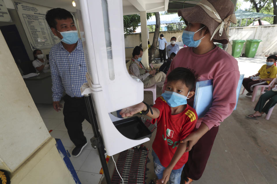 A young boy, center, disinfects his hands before receiving a shot of the Sinovac's COVID-19 vaccine at Samrong Krom health center outside Phnom Penh, Cambodia, Friday, Sept. 17, 2021. Prime Minister Hun Sen announced the start of a nationwide campaign to give COVID-19 vaccinations to children between the ages of 6 and 11 so they can return to school safely after a long absence due to measures taken against the spread of the coronavirus. (AP Photo/Heng Sinith)