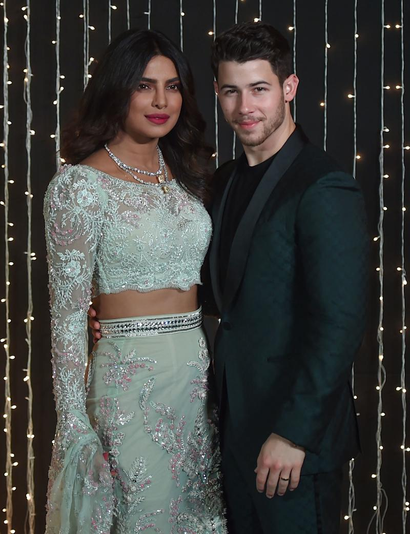 Priyanka Chopra and Nick Jonas pose together at a reception for their wedding in December.  (PUNIT PARANJPE via Getty Images)