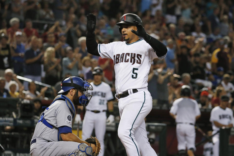 Arizona Diamondbacks' Eduardo Escobar (5) celebrates his two-run home run as Los Angeles Dodgers catcher Russell Martin, left, pauses at home plate during the sixth inning of a baseball game Friday, Aug. 30, 2019, in Phoenix. (AP Photo/Ross D. Franklin)