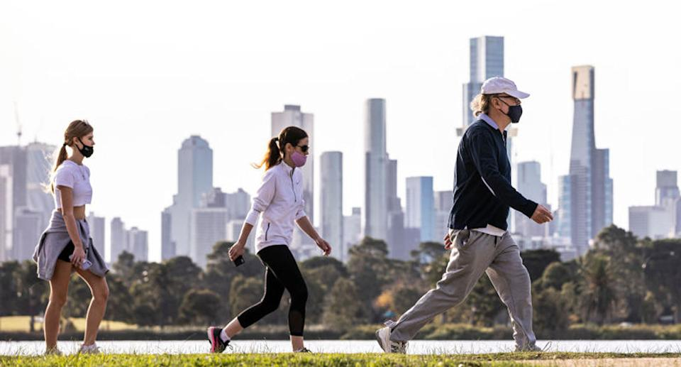Three Victorians in mask walk along the Yarra River bank.