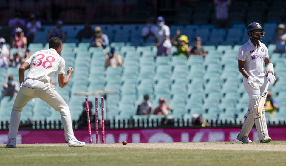 India's Cheteshwar Pujara, right, is out bowled by Australia's Josh Hazlewood, left, during play on the final day of the third cricket test between India and Australia at the Sydney Cricket Ground, Sydney, Australia, Monday, Jan. 11, 2021. (AP Photo/Rick Rycroft)
