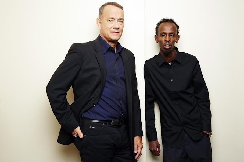 """This Sept. 27, 2013 photo shows actors Tom Hanks, left, and Barkhad Abdi, of """"Captain Phillips,"""" in New York. The film, about the 2009 hijacking of the US-flagged MV Maersk Alabama by Somali pirates, opens Oct. 11. (Photo by Dan Hallman/Invision/AP)"""