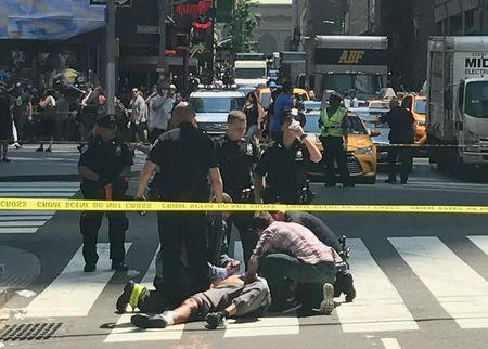 First responders and people help injured pedestrians after a vehicle struck pedestrians on a sidewalk in Times Square in New York, U.S., May 18, 2017. REUTERS/Jeremy Schultz