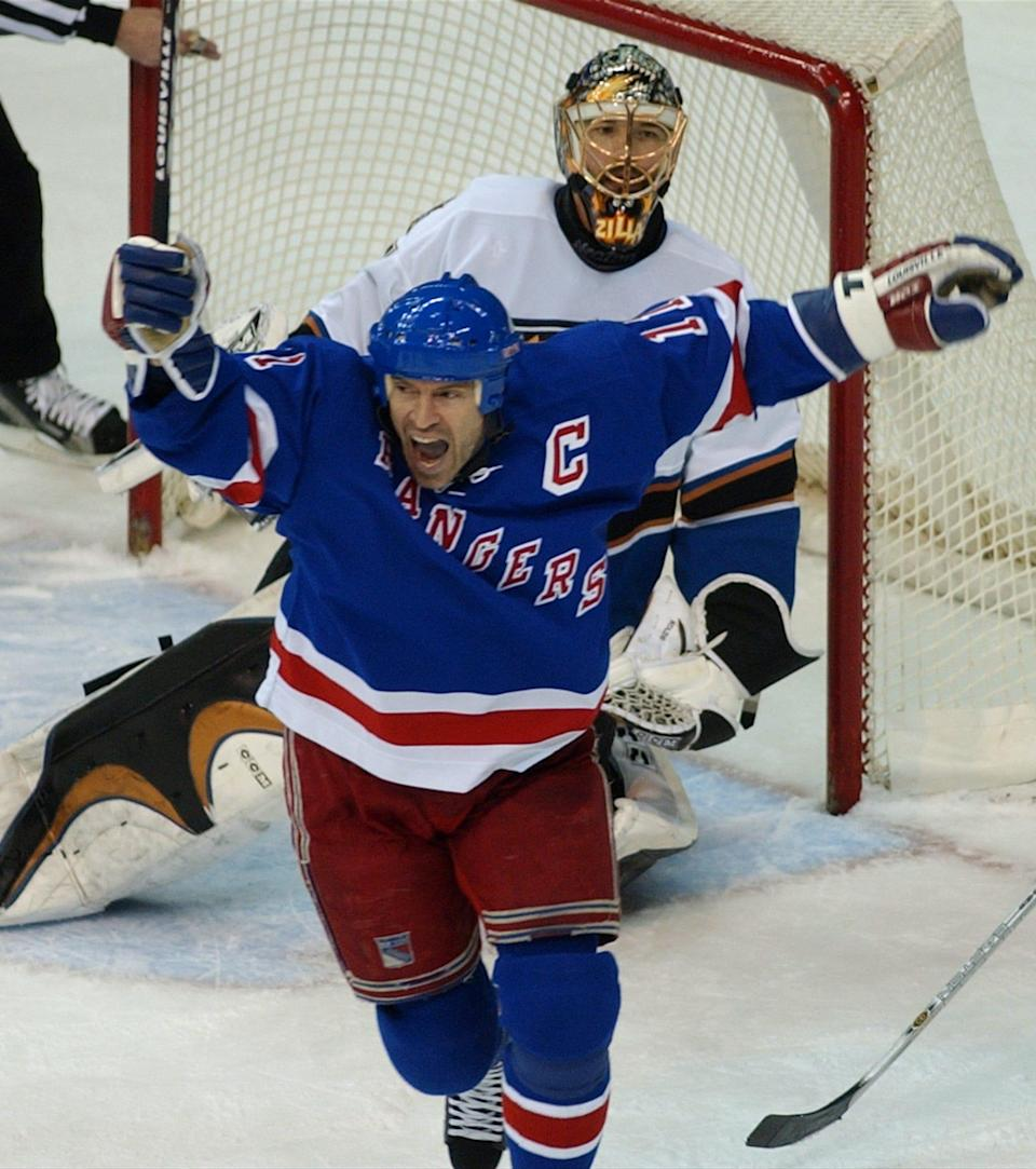 Rangers center Mark Messier celebrates a game-winning overtime goal in front of Capitals goalie Olaf Kolzig in the 2003 NHL playoffs.