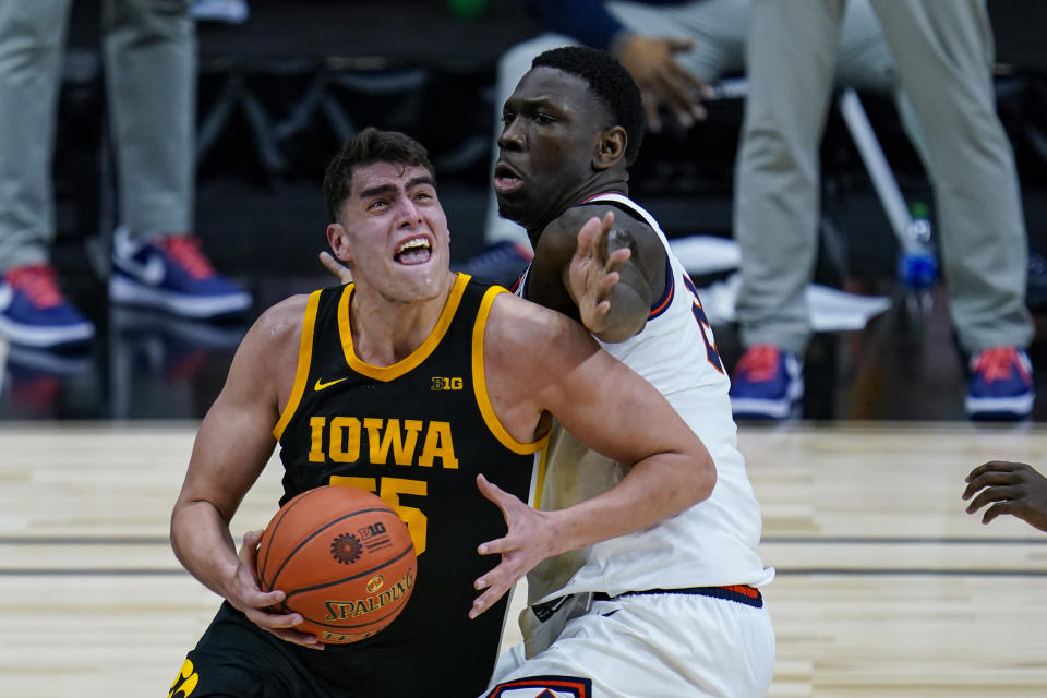 Illinois center Kofi Cockburn, right, defends against Iowa center Luka Garza (55) in the first half of an NCAA college basketball game at the Big Ten Conference tournament in Indianapolis, Saturday, March 13, 2021. (AP Photo/Michael Conroy)
